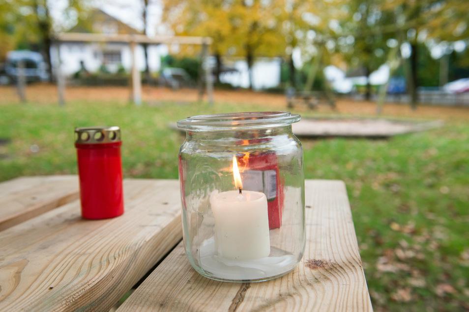 Kerzen stehen auf einem Kinderspielplatz auf einem Tisch. Auf dem Spielplatz ist am Vortag ein 22 Jahre alter Mann tot aufgefunden worden, die Ermittler gehen von einem Tötungsdelikt aus.