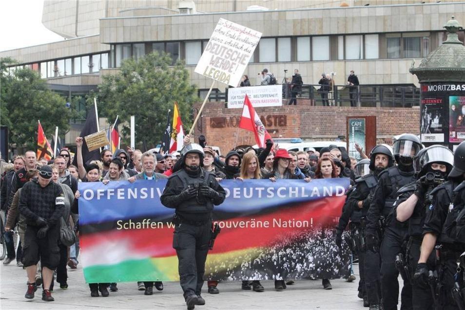 """Teilnehmer einer Demonstration der """"Offensive für Deutschland"""" gehen in Leipzig unter Polizeibegleitung mit Transparenten eine Straße entlang."""