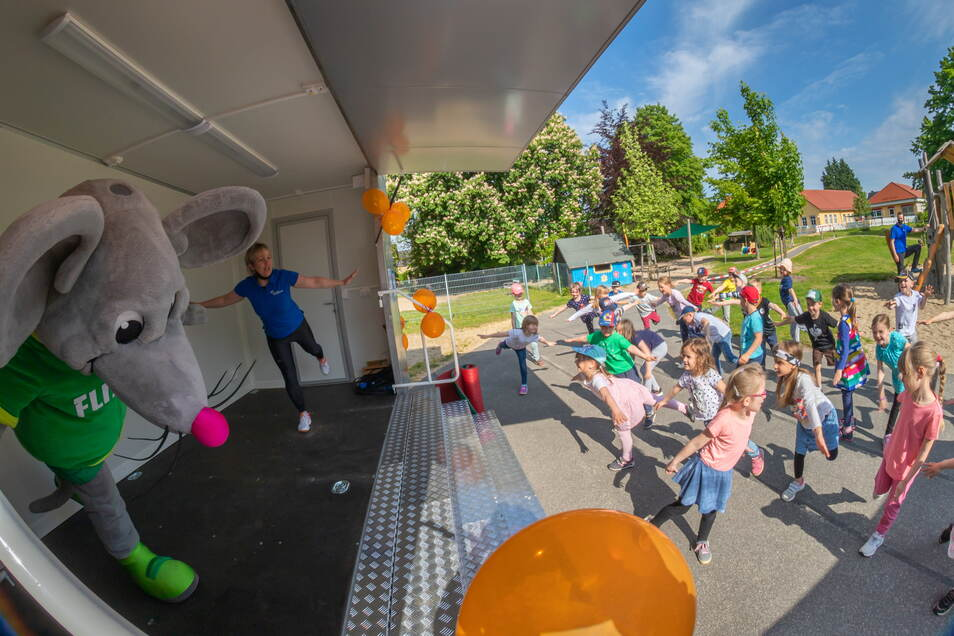 Sportmaus Flizzy und Jana Lommatzsch vom Kreissportbund führen mit den Kodersdorfer Kita-Kindern Sportübungen durch.