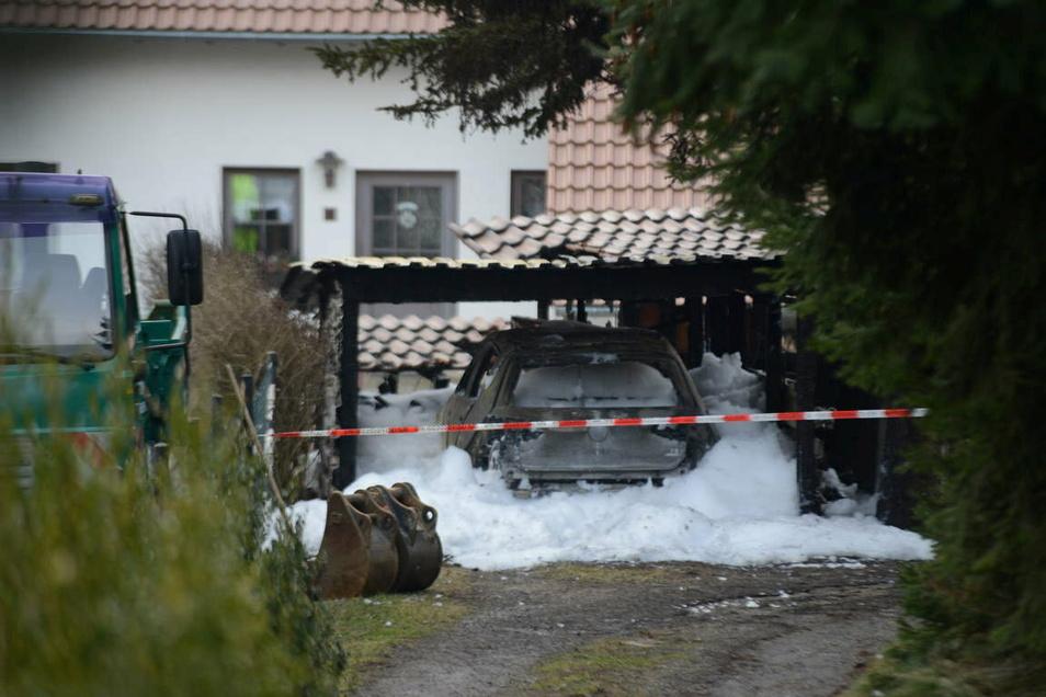 Löschschaum umhüllt den VW Golf, der unter einem Carport stehend in Brand geraten war.
