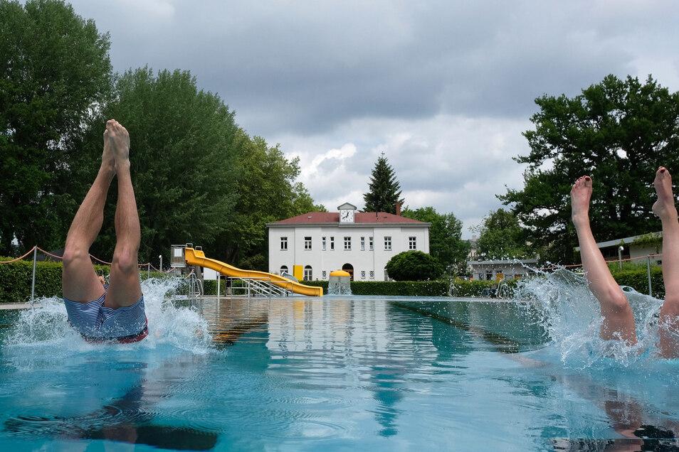 Ein junges Paar springt im Leipziger Schreberbad ins Wasser.