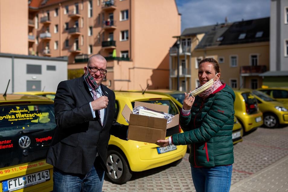 Stadtrat René Neuber von den Freien Wählern Freital übergibt Schutzmasken an Claudia Voigt vom Pflegedienst Rietzschel.