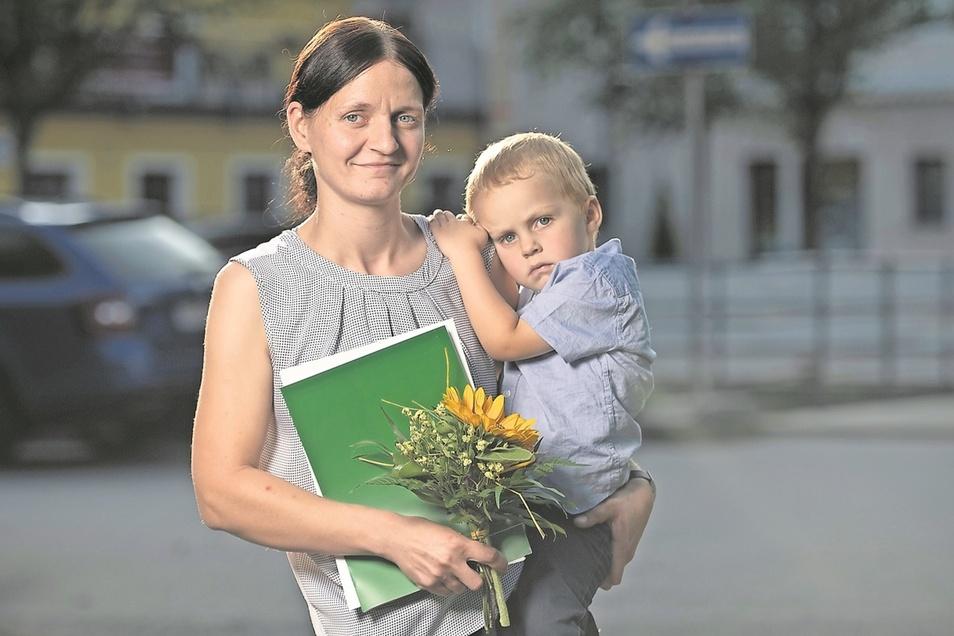 Erleichtert hält Cindy Friebel ihren Gesellenbrief in der Hand und ihren Sohn Denny auf dem Arm.
