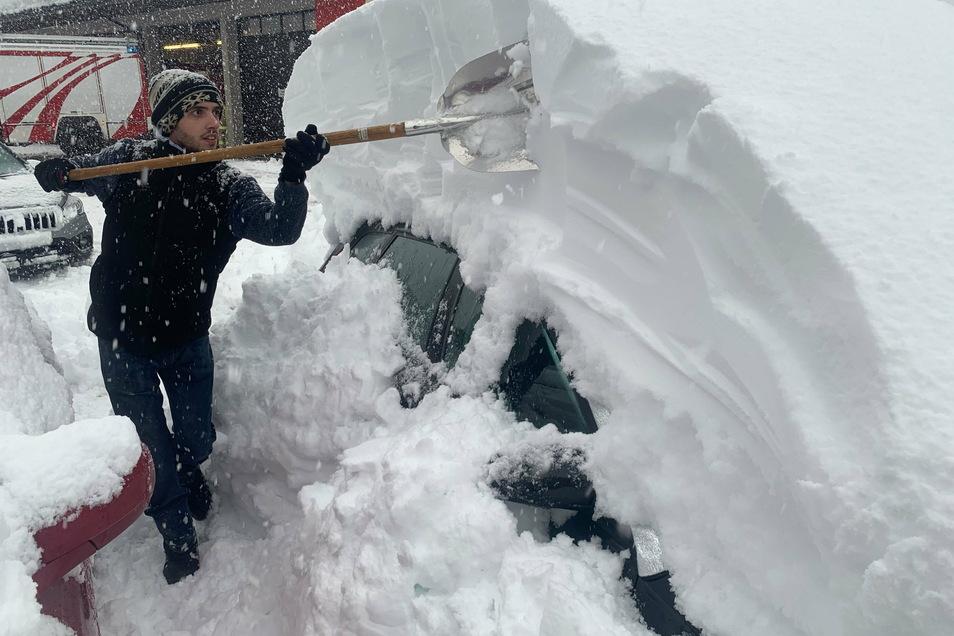 Patrick Werth befreit im österreichischen Sillian mit einer Schaufel sein Auto von den Schneemassen.