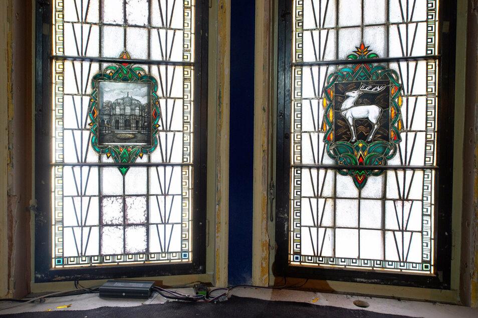 Der Weiße Hirsch steht als Motiv in der Mitte des Fensterensembles, daneben Bilder vom Zwinger oder Schlössern der Region.