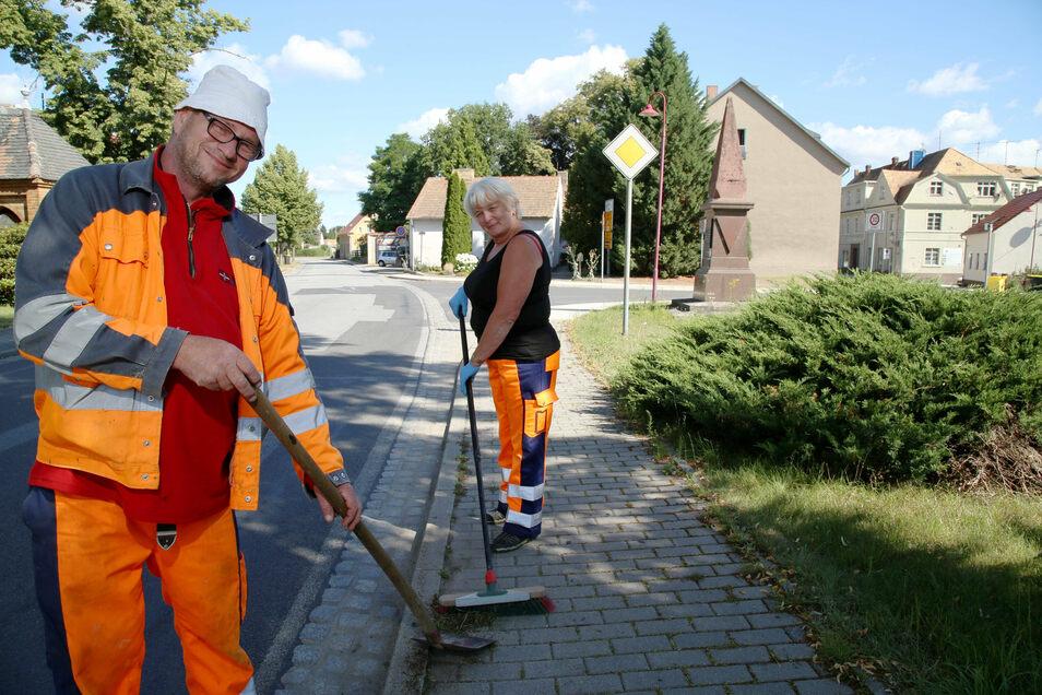 Bauhofchef Roland Firl und Mitarbeiterin Beate Schwank kehren die Ablaufrinne und den Fußweg an der Görlitzer Straße in Rothenburg. Nach dem Willen der Stadträte soll das Straßenbild künftig noch besser werden.