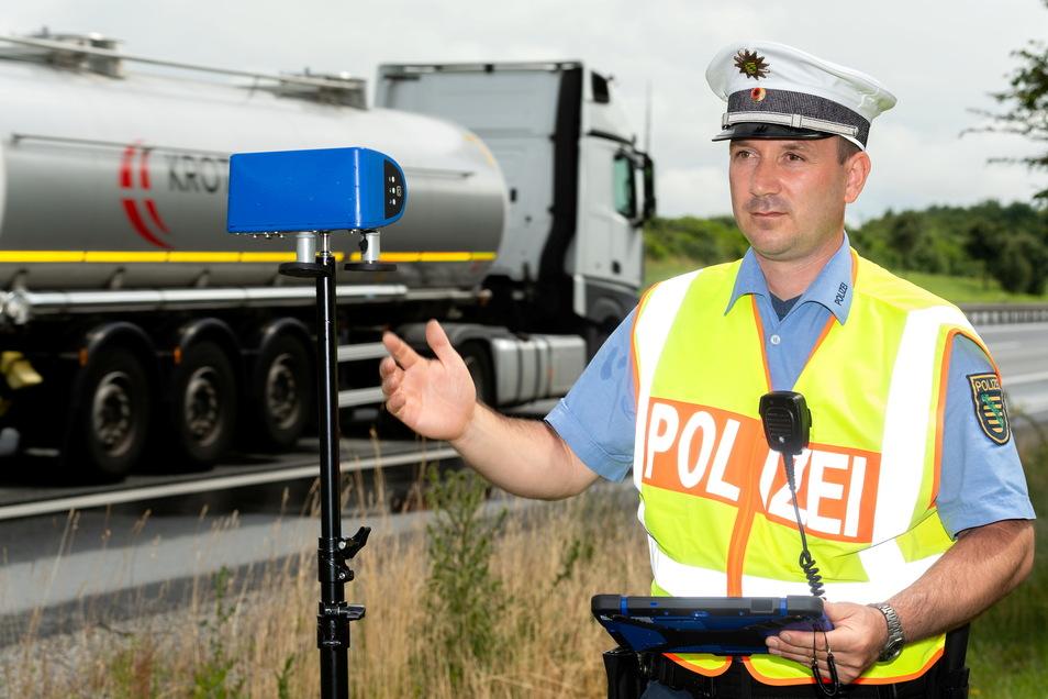 Polizeihauptkommissar Tino Hausdorf überprüft an der A 4 bei Bautzen mit einem speziellen technischen System die Informationen des digitalen Fahrtenschreibers eines vorbeifahrenden Lkw.