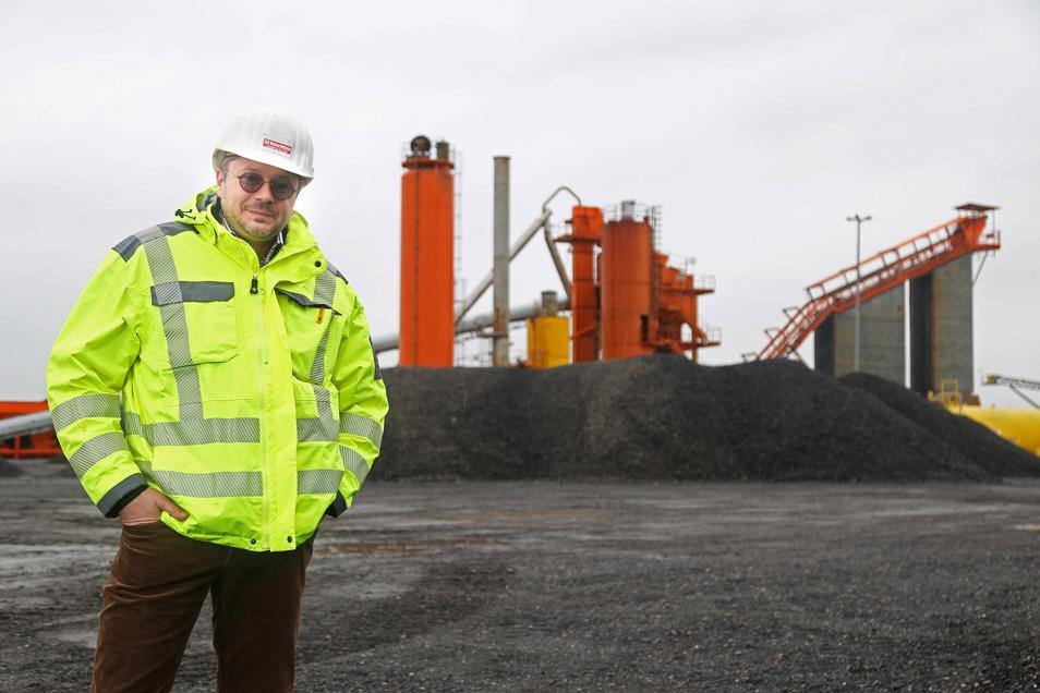 Dirk Menninger ist Technischer Leiter bei den ard-Baustoffwerken. Im Hintergrund Halden aus Alt-Asphalt, der im eigenen Asphaltwerk wiederverwendet wird.