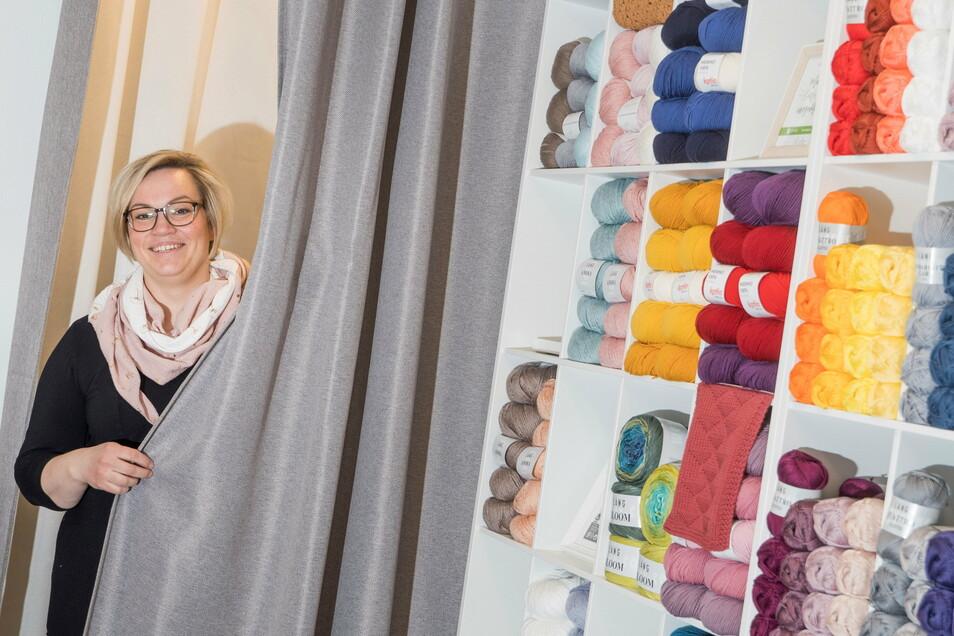 Im hinteren Bereich ihres Ladens gibt es eine Woll-Auswahl. Außerdem ist eine Umkleidekabine vorhanden, in der Kleidung probiert werden kann, die die Änderungsschneiderei gearbeitet hat.
