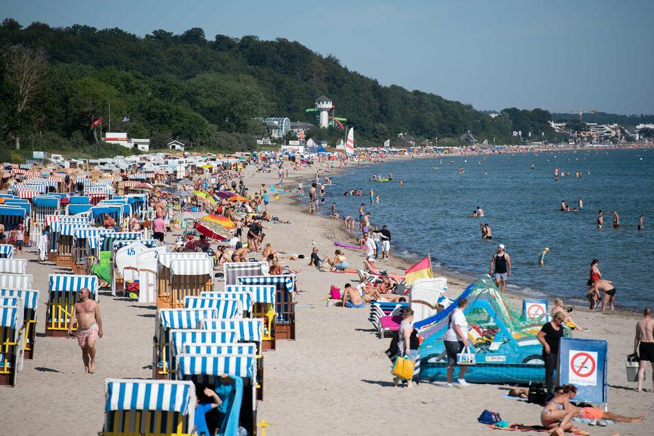 Zahlreiche Menschen sind schon in den Morgenstunden am Timmendorfer Strand unterwegs.