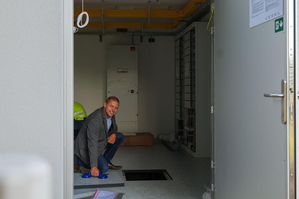 Bürgermeister Mirko Knöfel schaut in das Innere des Verteilers, wo demnächst die Glasfaseranschlüsse von zwölf Ortsteilen zusammenlaufen.