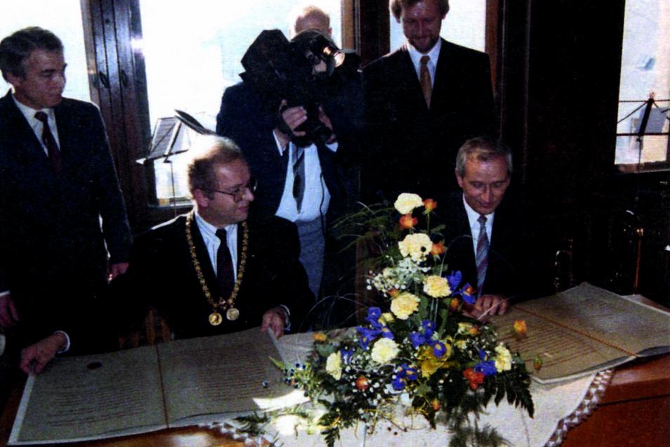 Im Beisein von Dietmar Hack (links) und Jost Handtrack (rechts stehend), den Initiatoren der Städtepartnerschaft von Landsberg am Lech und Waldheim, unterzeichnen Oberbürgermeister Franz Xaver Rößle und Bürgermeister Karl-Heinz Teichert am 10. Novemb