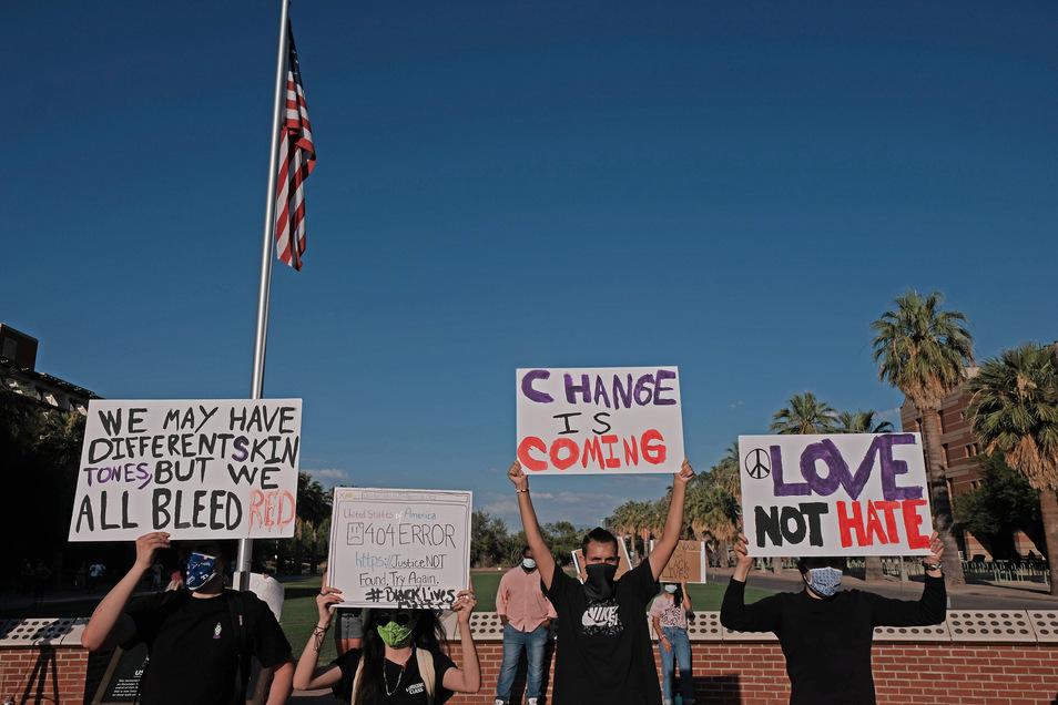 Demonstranten halten an der Universität von Arizona Plakate hoch.