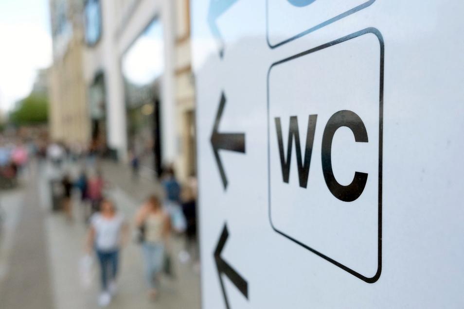 Ein Schild weist in Leipzigs Innenstadt den Weg zu einer öffentlichen Toilette.
