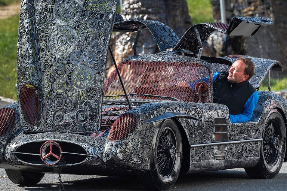 Der Dorfhainer Unternehmer Jens Jähnig sitzt in einem Mercedes, der ganz aus Schrott gefertigt wurde. Auf dem Gelände seiner Firma in Dorfhain kann man sich die Skulpturen anschauen.