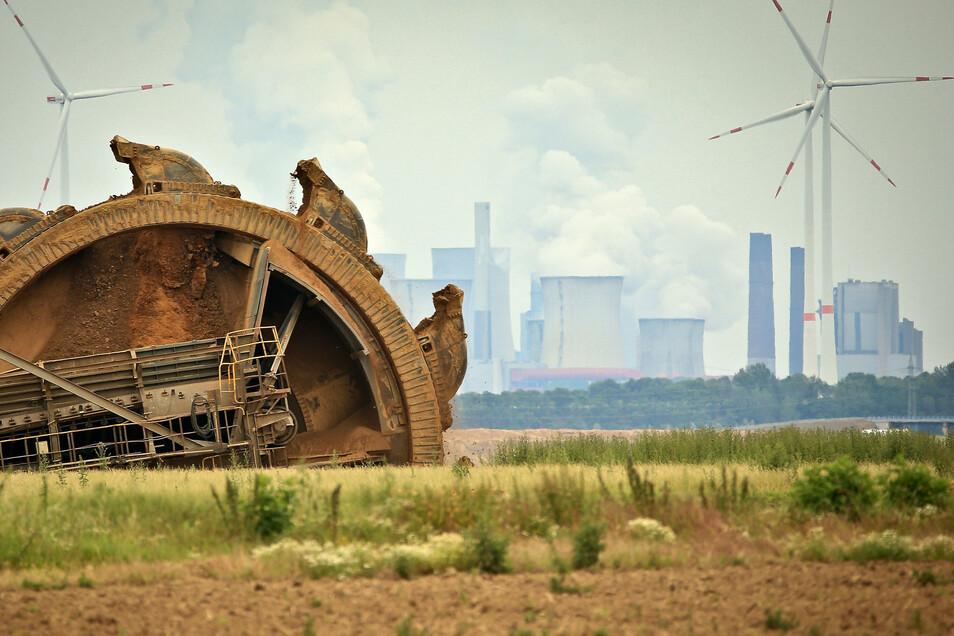 Ein Braunkohlebagger baggert im Tagebau Garzweiler, im Hintergrund steht ein Kraftwerk hinter Windrädern. Der Bundestag verabschiedet in seiner 171. Sitzung das Kohleausstiegsgesetz.