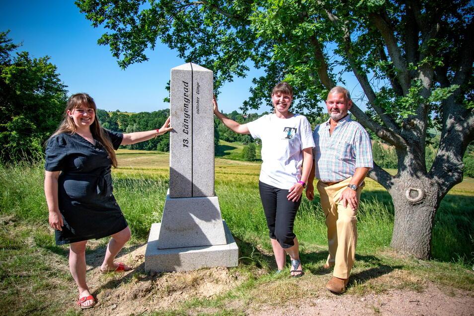 Karla Just, Bianca Ulbricht und Gerd Pfeifer stehen am Obelisk, der auf den 13. Längengrad östlicher Länge hinweist.