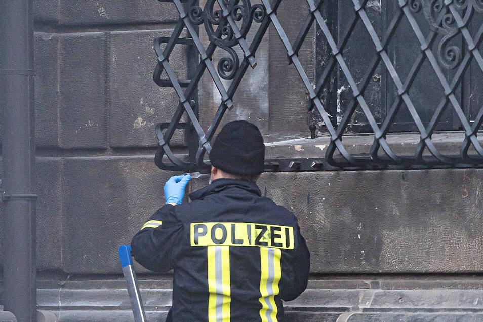 Ein Polizist untersucht das von den Einbrechern geöffnete Fenstergitter, durch das sie ins Grüne Gewölbe eingestiegen sind.
