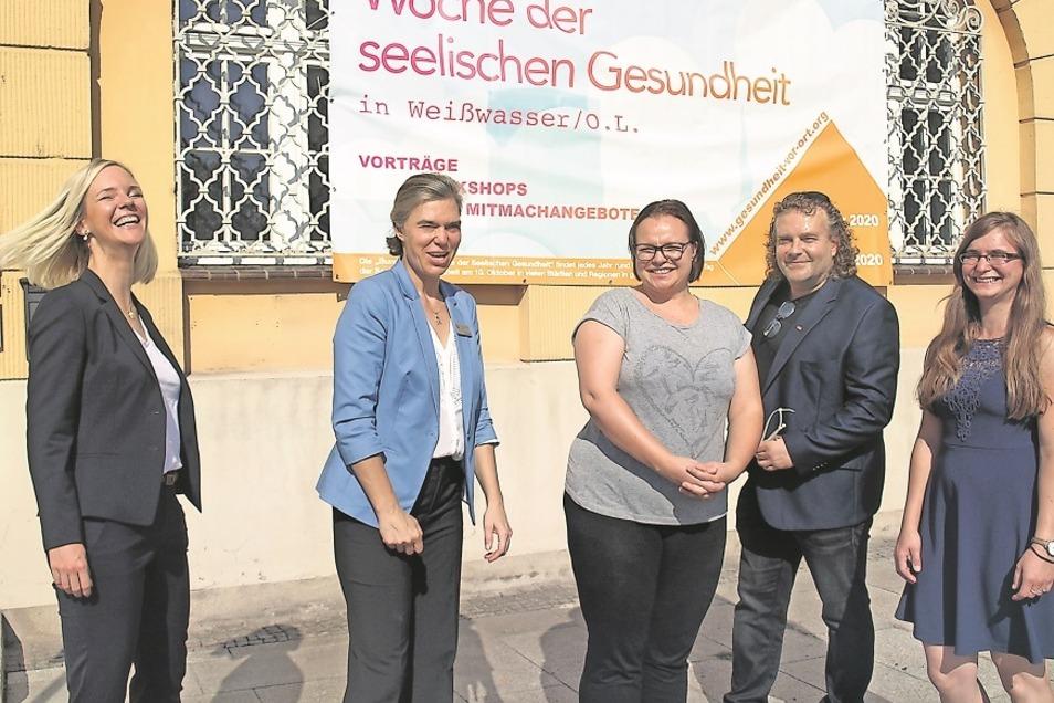 Unterstützer der Woche seelischer Gesundheit, wie Manuela Thomas und Romy Garner (li.) und Bianca Strohbach (re.) am Hinweisplakat am Rathaus Weißwasser
