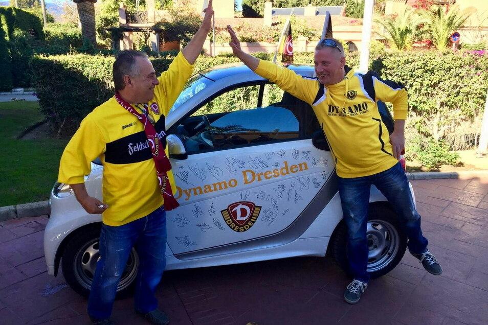 Fernando Hayn (links) mit seinem Bruder Norbert vor seinem Smart. Seit 2017 zieren das Auto nicht nur Dynamo-Embleme und Schriftzüge, sondern auch die Autogramme aller damaliger Dynamo-Spieler.