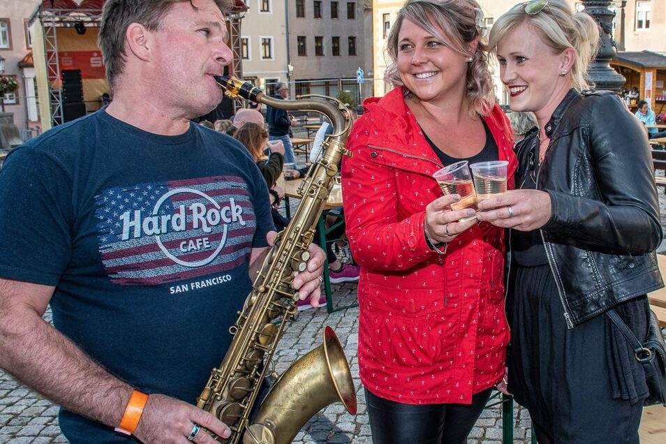 Tino Ludwig spielt für Lisa Schaarschmidt (mitte) und Katja Auerbach ein Ständchen beim diesjährigen Leisniger Weinfest.