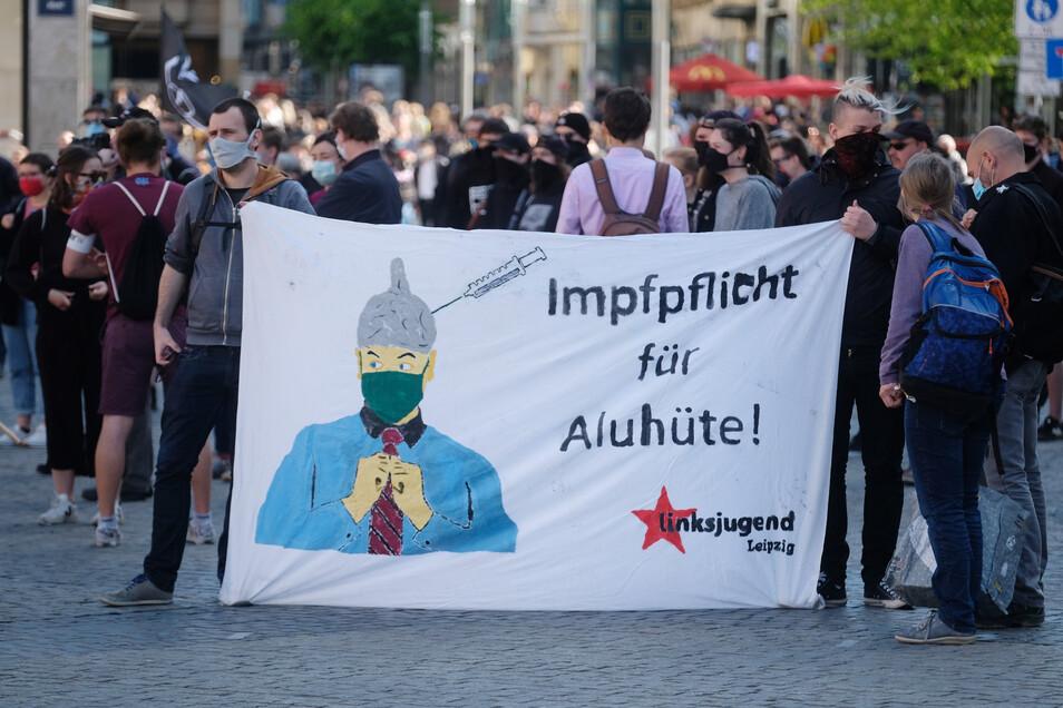 Leipzig: Teilnehmer einer Demonstration protestieren mit einem Transparent mit der Aufschrift «Impfpflicht für Aluhüte» gegen eine Kundgebung, die gegen die Corona-Maßnahmen protestiert. Mehrere hundert Menschen versammelten sich zum Protest gegen die Cor