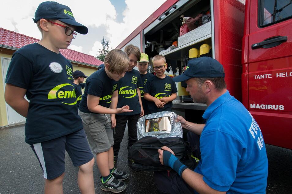 Stefan Voß, Ortswehrleiter von Meinsberg, zeigt den Mädchen und Jungen der Kinderfeuerwehr, welche besondere Ausrüstung bei starker Hitze neben den Atemschutzgeräten eingesetzt wird, wie der spezielle Flammschutz aus Aluminium.
