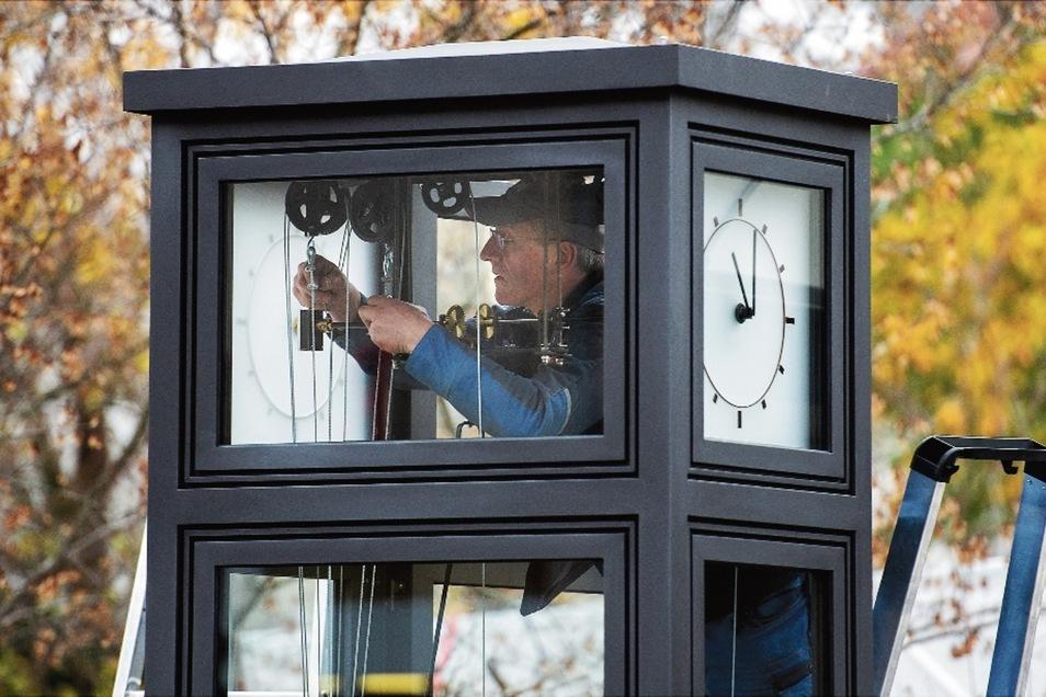 Der Herr über die Zeit: Turmuhrmacher Andreas Zschipke aus Pirna montiert am Sonnabend die neue Standuhr an der Hauptstraße in Coswig, gegenüber der Sparkasse.