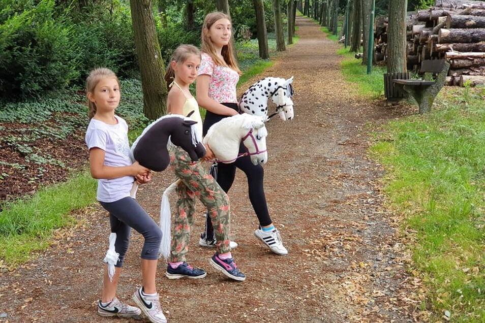 Ina, Amalia und Sofia Chigladze (v.l.) beim Ausritt mit ihren Steckenpferden auf dem Hutberg.