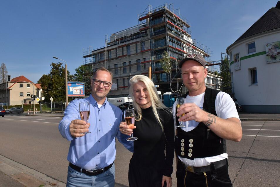 Karsten und Nicole Tobias trinken mit Bauleiter Dennis Abraham ein Gläschen beim Richtfest.