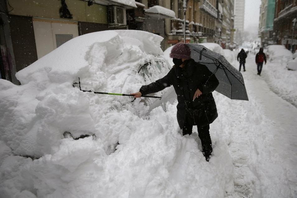 Eine Frau befreit in Madrid ihr Auto von einer hohen Schneeschicht.