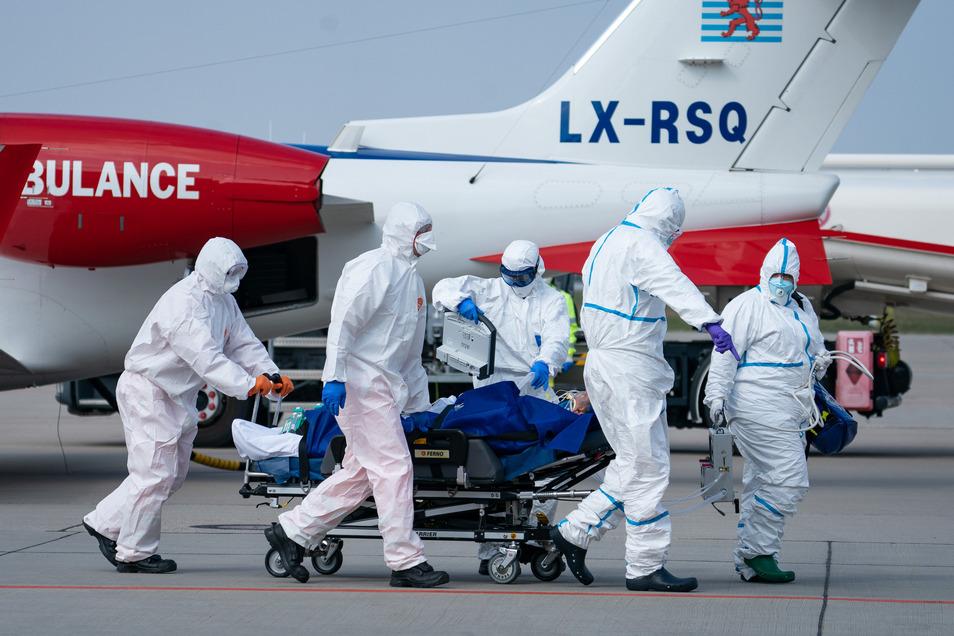Ein französischer Corona-Patient wird von medizinischen Fachkräften auf dem Flughafen Dresden in einen Intensiv-Krankenwagen überführt. Insgesamt sind am Samstag bislang zwei Covid19-Patienten aus Frankreich auf dem Flughafen Dresden gelandet.