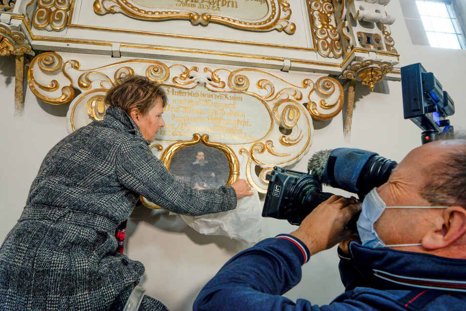 Restauratorin Uta Matauschek enthüllt das Bildnis von Gregorius Mättig, das sich am Mättig-Epitaph im Dom St. Petri in Bautzen befindet. Das Epitaph ist jetzt nach zehnjähriger Restaurierung wieder vollständig.