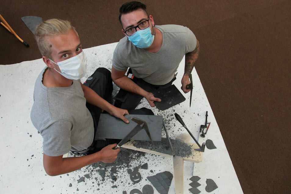 Zeigen wie es geht: Dachdecker-Azubi Dennis Wenzel (li.) zeigt zusammen mit Dachdeckermeister Paul Bredner aus Bad Schandau, wie Schiefer bearbeitet wird.