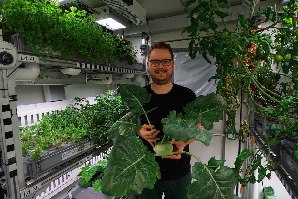 Paul Zabel steht mit geerntetem Kohlrabi im Gewächshaus Eden-ISS.