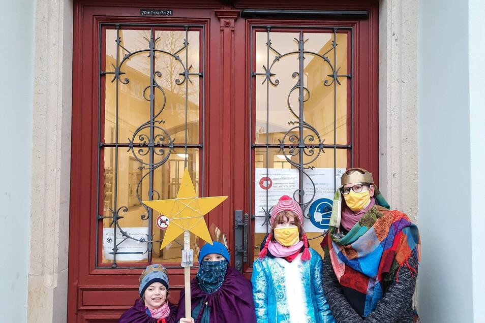 Mutter Sandy Klups mit ihren Kindern Josephine, Jaspar und Mina bringen den Segen Gottes auch 2021 am Bürgerhaus Bannewitz an.