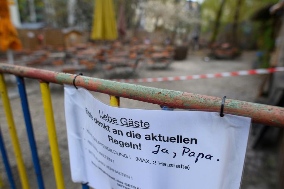 Ein Zettel mit dem Hinweis für die aktuellen Corona-Regeln hängt in der Dresdner Neustadt an einem Zaun vor einem Biergarten. Die Sieben-Tage-Inzidenz beträgt aktuell in Dresden 108,8 - unter 100 an fünf Tagen in Folge dürfen Biergärten und Co. öff