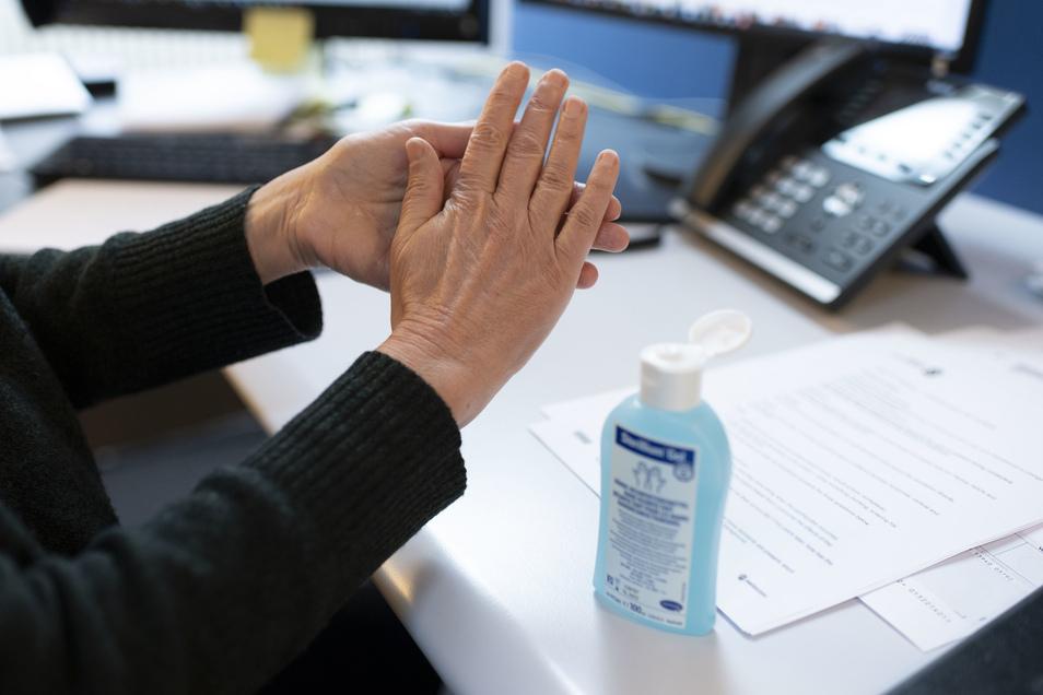 Eine Person reibt sich am Arbeitsplatz die Hände mit einem Desinfektionsmittel ein. Das Coronavirus hat auch Auswirkungen auf die Arbeitswelt.