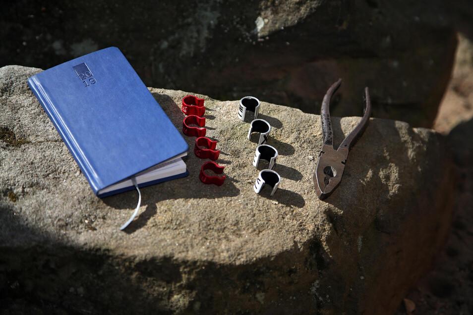"""Die """"Ausweise"""" der Falken: links Habitatringe - rot steht für Felsenbrüter - und rechts groß beschriftete Kennringe zur Ablesung mittels Fernglas."""