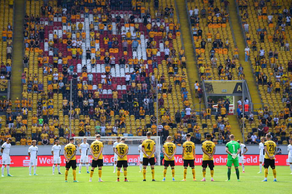 Die Spieler beider Mannschaften stehen während einer Schweigeminute für die Opfer der Hochwasserkatastrophe am Mittelkreis.