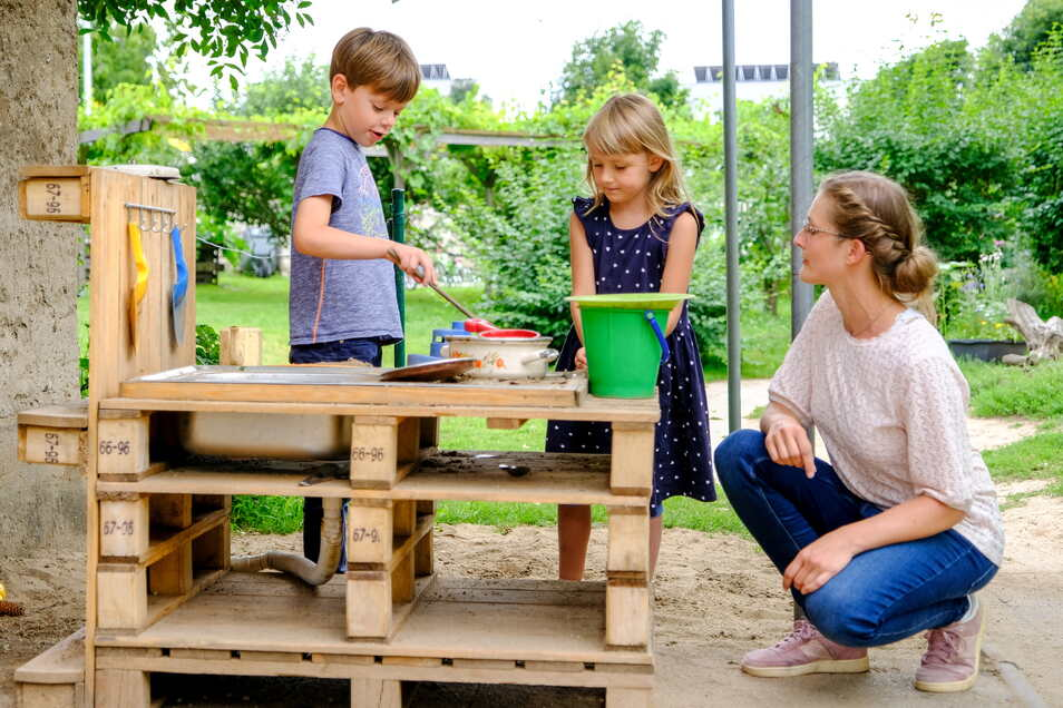 """Emil und Evelina backen in der Matschküche der Kita """"Kinderkreis Natur, Heimat und Gesundheit"""" einen Sandkuchen. Debora Centner schaut ihnen dabei zu. Die Sprachfachkraft möchte mit Kindern und Eltern zusammen weitere neue Spielbereiche schaffen."""