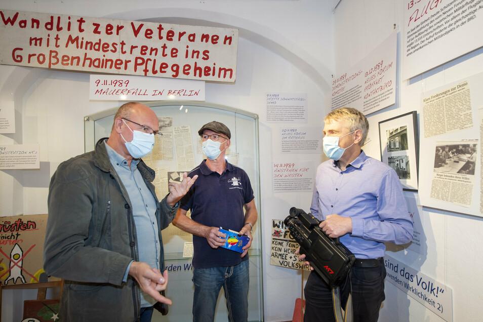 Peter Grünewald (M.) übergibt dem Leiter des Museums Alte Lateinschule Jens Schulze-Forster (r.) und Geschäftsbereichsleiter Stadtkultur Matthias Schmieder in der Sonderausstellung zur friedlichen Revolution seine Filmkamera vom Wendeherbst '89.