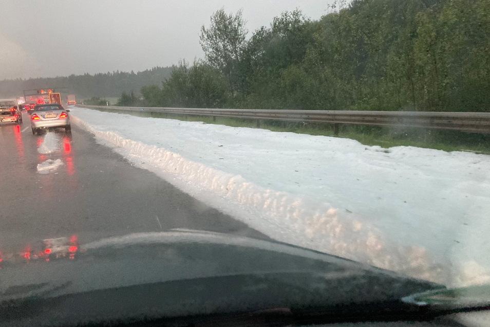 26.07.2021, Bayern, Eine dicke Schicht mit Hagelkörnern liegt auf dem Randstreifen der Autobahn 8 in Irschenberg/Bayern.