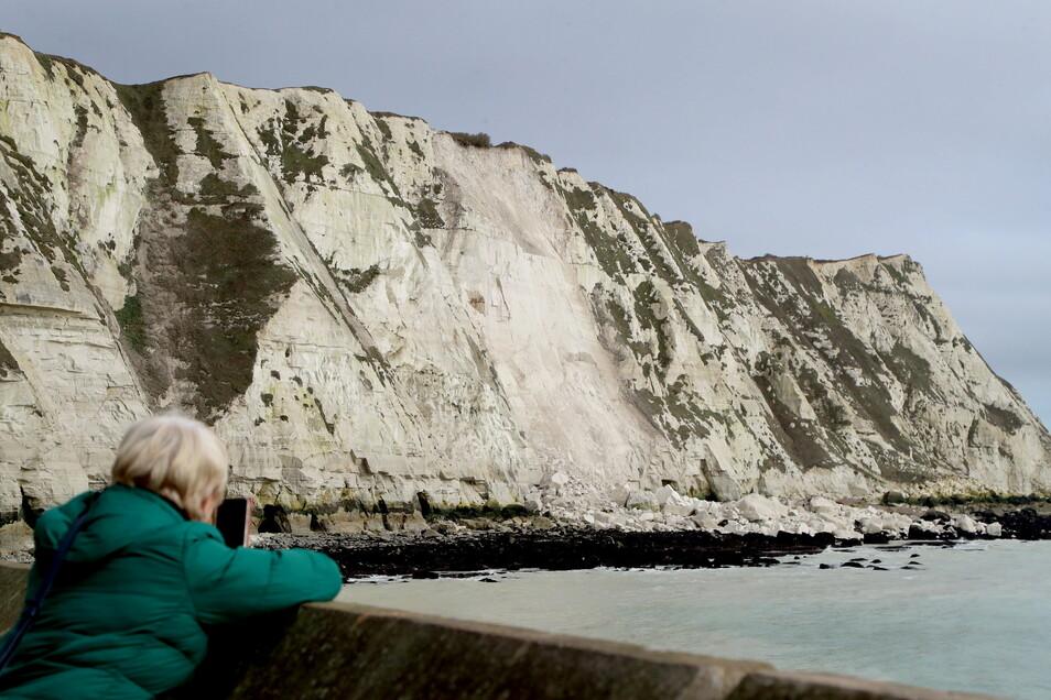 Eine Frau fotografiert die weißen Klippen nahe Dover, die eingestürzt sind. Ein großer Brocken der berühmten weißen Klippen nahe Dover ist in den Ärmelkanal gestürzt.