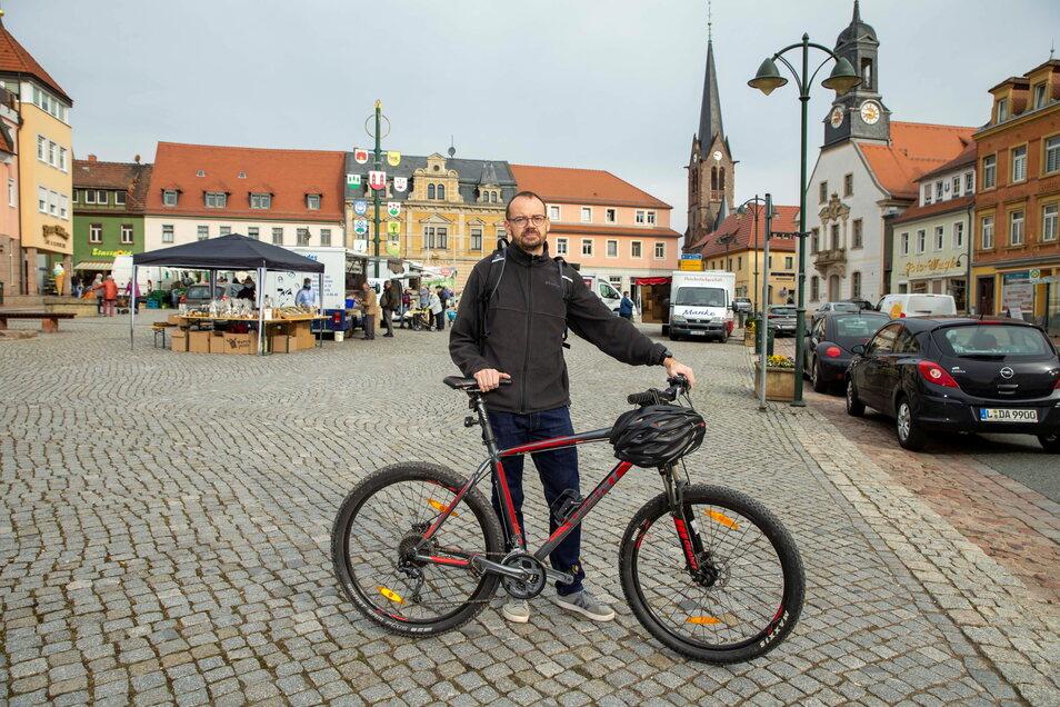 Ronny Haupt steht mit dem Rad auf dem Marktplatz in Wilsdruff. Er beklagt, dass es in der Stadt keine oder nur wenige Radwege gibt. Gerade in der Altstadt sei das ein Problem, da aus den Gassen kommende Fahrzeuge, ihn schnell übersehen.