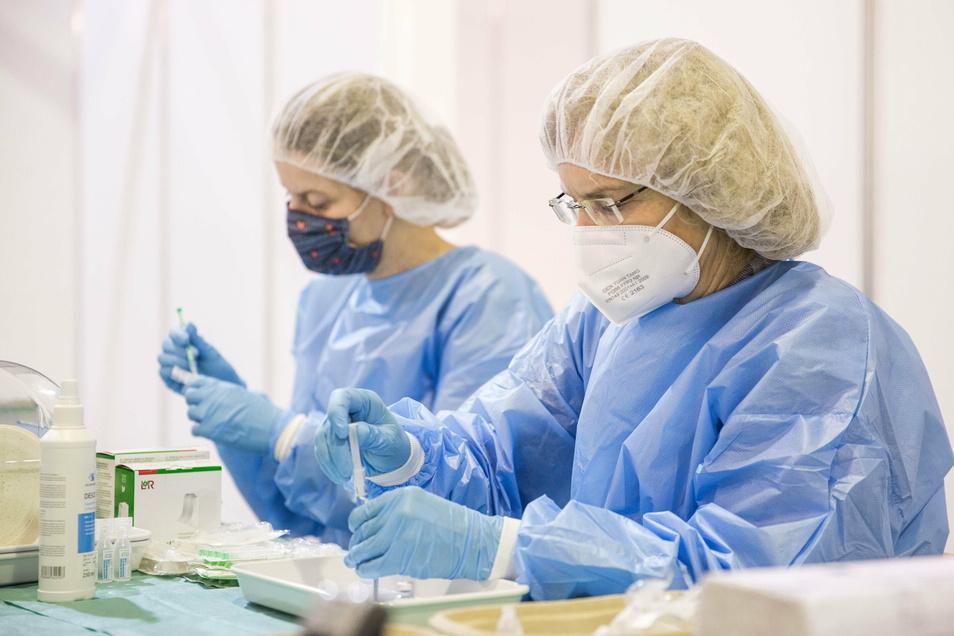 Angemischt und aufgezogen wird der Biontech-/Pfizer-Impfstoff im Hintergrund. Sylva Richter und Marina Hennig arbeiten zwischen den Impfstrecken im Dresdner Impfzentrum.