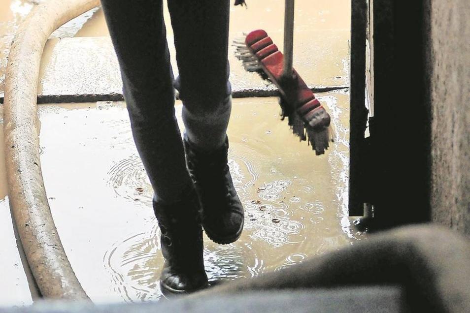 Unverdrossen: Mit Besen, Pumpen und Schläuchen kämpften Helfer stundenlang gegen den Dreck.