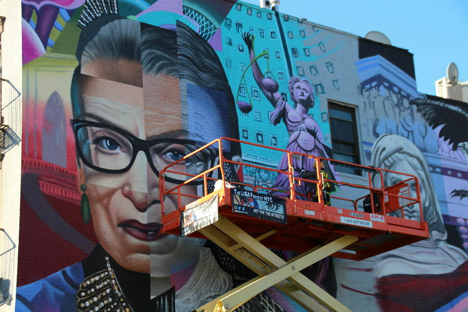 Künstler legen letzte Hand an ein buntes Gemälde an einer Hauswand im East Village in Manhattan an.