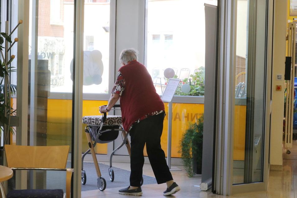 Eine Heimbewohnerin geht in einem Pflegeheim mit einem Rollator durch den Gemeinschaftsbereich.