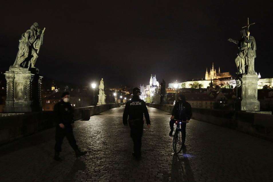 Noch gelten strenge Regeln in Tschechien: Polizisten kontrollieren auf der ansonsten menschenleeren Karlsbrücke in Prag einen Radfahrer.